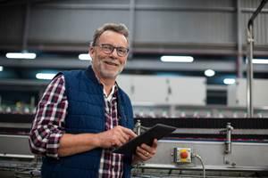 Man in job shop using tablet