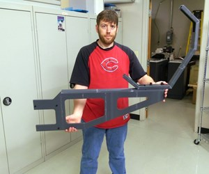 man holds 3d-printed bracket prototype