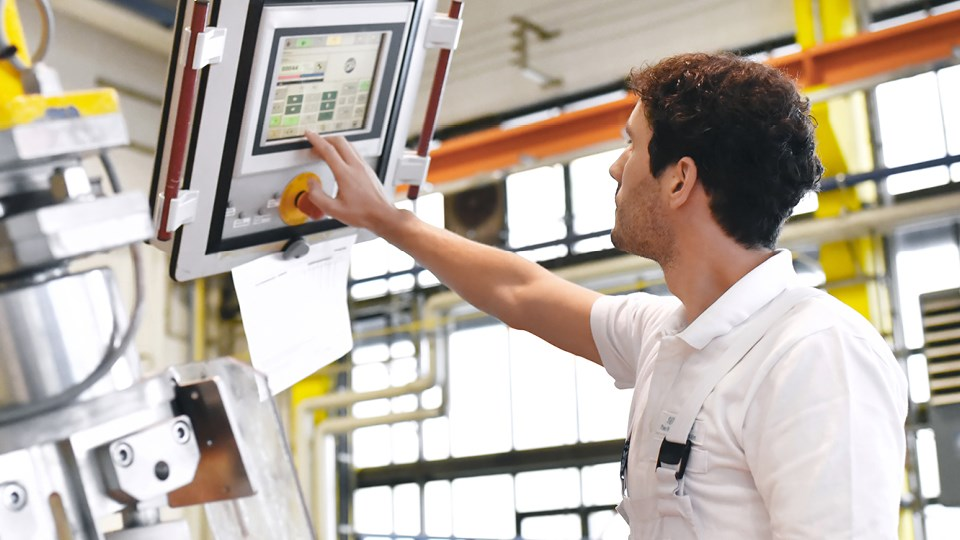 Man operating MMT technology in shop setting.