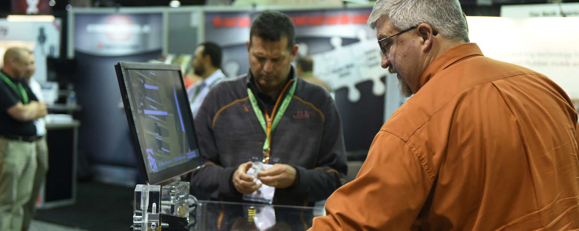 Two gentlemen discussing technology on the Amerimold show floor.
