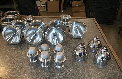 Una selección de componentes de moldes de vidrio muestra el acabado de espejo que requieren algunas de estas piezas.