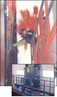 An operator paints one side of a rail car door