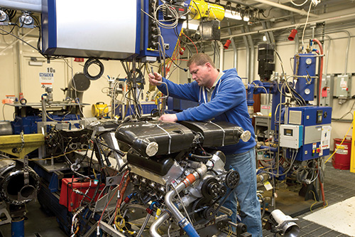 A C7 engine being setup on a dyno at the GM Performance and Racing Center. The facility has four dynos, two gas-powered engine dynos and a gas-powered driveline dyno and an electric driveline dyno.