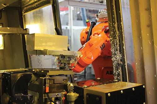 robot arm placing workpiece into machining center