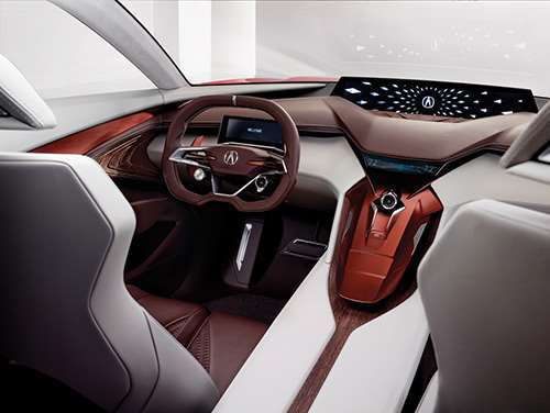 Inside, there is a double-layered instrument panel. The large center screen is curved. Note the use of wood and leather, the types of materials characteristic of luxury vehicles. And speaking of wood: they even use it to craft the speaker grilles, certainly an unexpected touch.