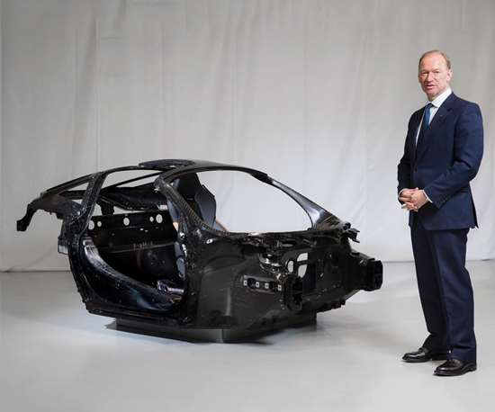 """Mike Flewitt, CEO of McLaren Automotive, next to a """"Monocage"""" carbon fiber chassis. McLaren will develop and make carbon fiber chassis in the UK for the first time."""