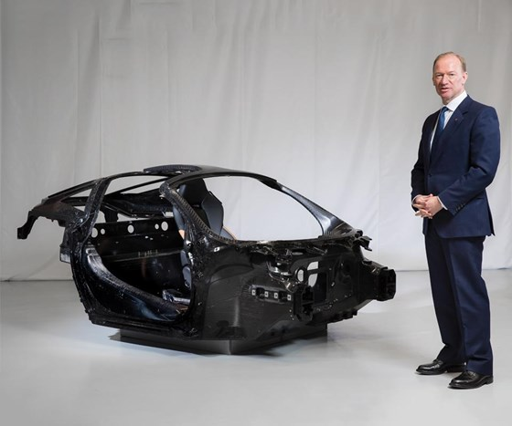 "Mike Flewitt, CEO of McLaren Automotive, next to a ""Monocage"" carbon fiber chassis. McLaren will develop and make carbon fiber chassis in the UK for the first time."