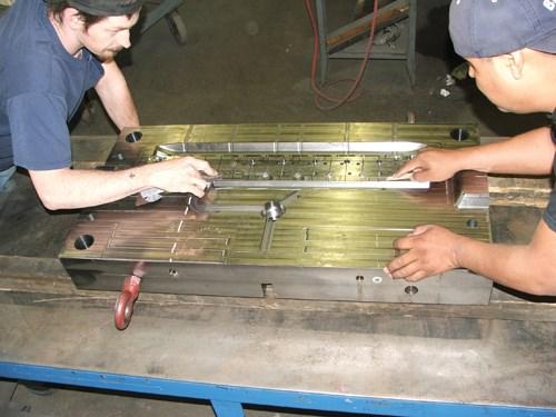 Two polishers polish a mold