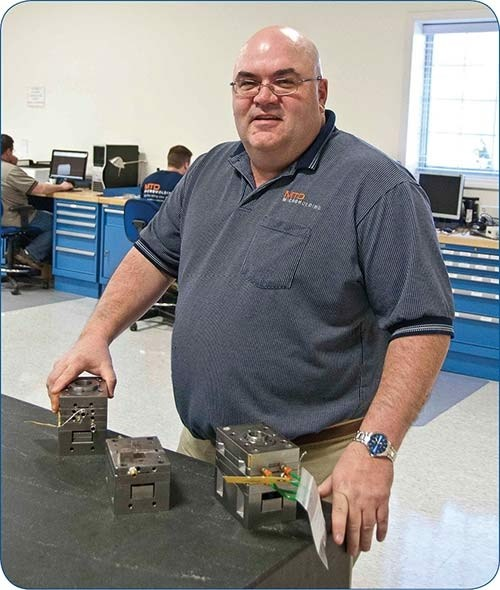 MTD president Dennis Tully with some of his firms micro molds.