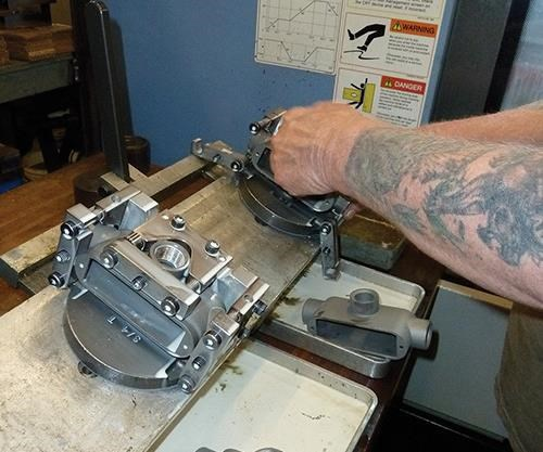 Here, machined parts just removed from the VMC are being unclamped and replaced with unthreaded workpieces.