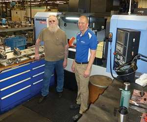 Here you can see how the placement of the tool cabinet, the pallet loading/unloading station and the machine tool itself allow Mr. Simpson (with Ryan Hart, process engineer, at right) to reach all areas of activity in his workstation with minimum twisting motion.