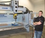 Kyle Castor stands in front of a five-axis router with arms crossed.