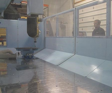 Kyle Castor looks in on the machining process through the window