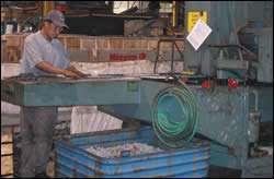Parts enter a belt sander