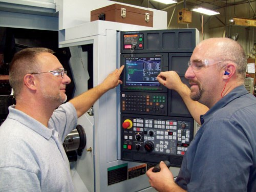 men in front of CNC control