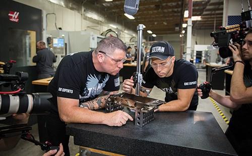 Titan Gilroy and his son Chris Gilroy inspect a part; cameraman Joel Sandvos films