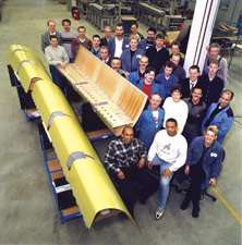 The Stork Fokker manufacturing team for the A380 leading edge poses with three finished J-nose assemblies.