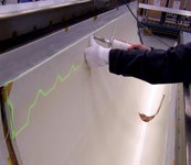 A technician prepares to lay up a semipreg ply, using a laser projection system.