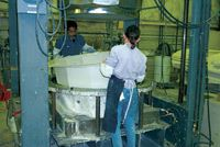 As soon as the mold begins to cool, two operators remove the cured part and prepare it for shipment.