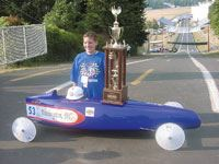 Johnny Weissgerber poses with his 3rd Place trophy and car at the top of the 2001 All-American Soap Box Derby race course.