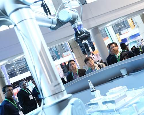 Men looking at a cobot at IMTS