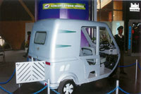 The three-wheeler's entire body, including rear bumper and seat pedestals, is a composite construction, optimizing the HEV's weight for fuel economy.
