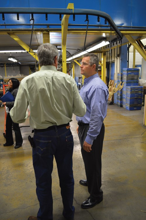 Hentzen Coatings' John Mort talks with a customer while demonstrating the new CARC powder topcoat.