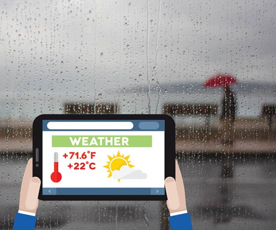 Tablet with weather displayed while looking out the window at rain.