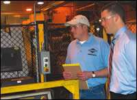 Chris Peters (right) checks on machining line with Greg Hartwig