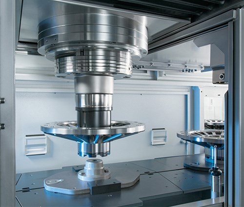 This view inside the Emag VL 8 turning center shows the machine's pick-up spindle lifting a workpiece from the lateral conveyor belt to carry it to the machining area. The spindle has a chuck diameter of 500 mm and accepts workpiece diameters ranging to 400 mm.