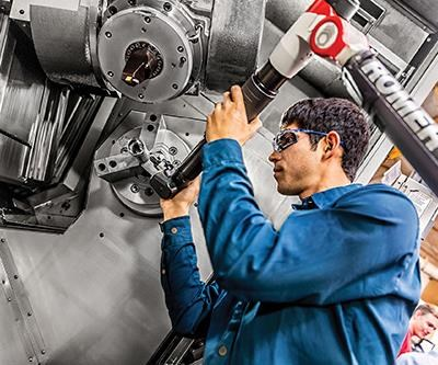 Wolfram's Robert Perez uses a portable CMM to inspect the final product in the machine.
