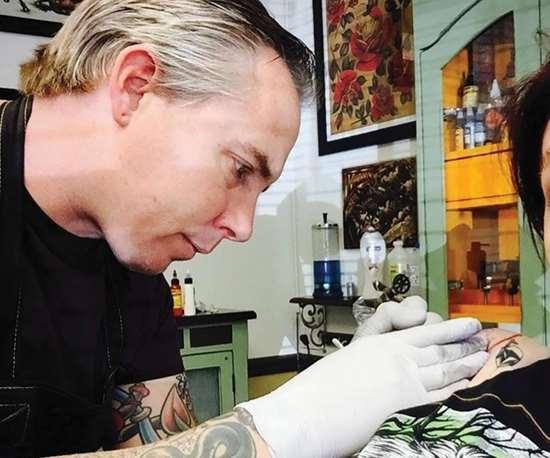 Dan Kubin tattoos a customer's shoulder