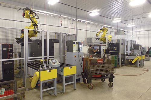 robot arm above and behind the Okuma lathes