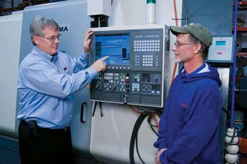 Randy Lewis of LNS America demonstrates the e-Connect system to Robert Silcott, lead machinist at Nilpeter.