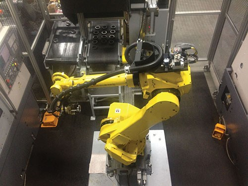 Two fixtureless, powered flat belt conveyors transport raw parts to the robot for processing and move completed parts to a manual unloading station.