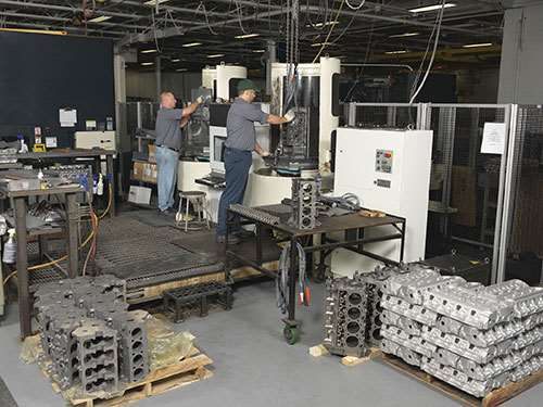 employees loading the Makino Machining Complex cell