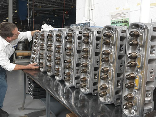 Roger Burkel inspects a row of cylinder heads