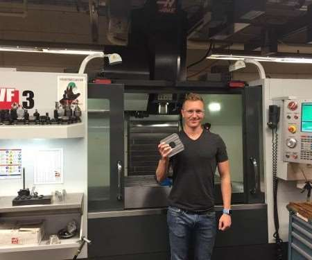 Mechanical engineer Dakota Bass is seen here with one of the machining centers used to manufacture satellite launchers at CubeSat.