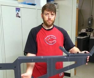 man holds 3d-printed bracket prototype