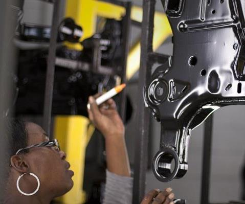 woman inspects parts