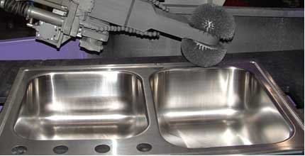 By simply changing brushes, the type of finish of this sink finishing machine can be altered to adapt to market demands.