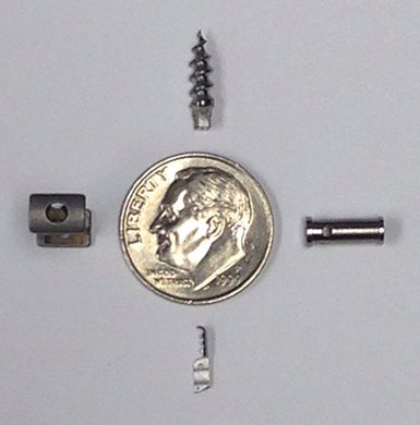 a dime next to small machined parts to show their size