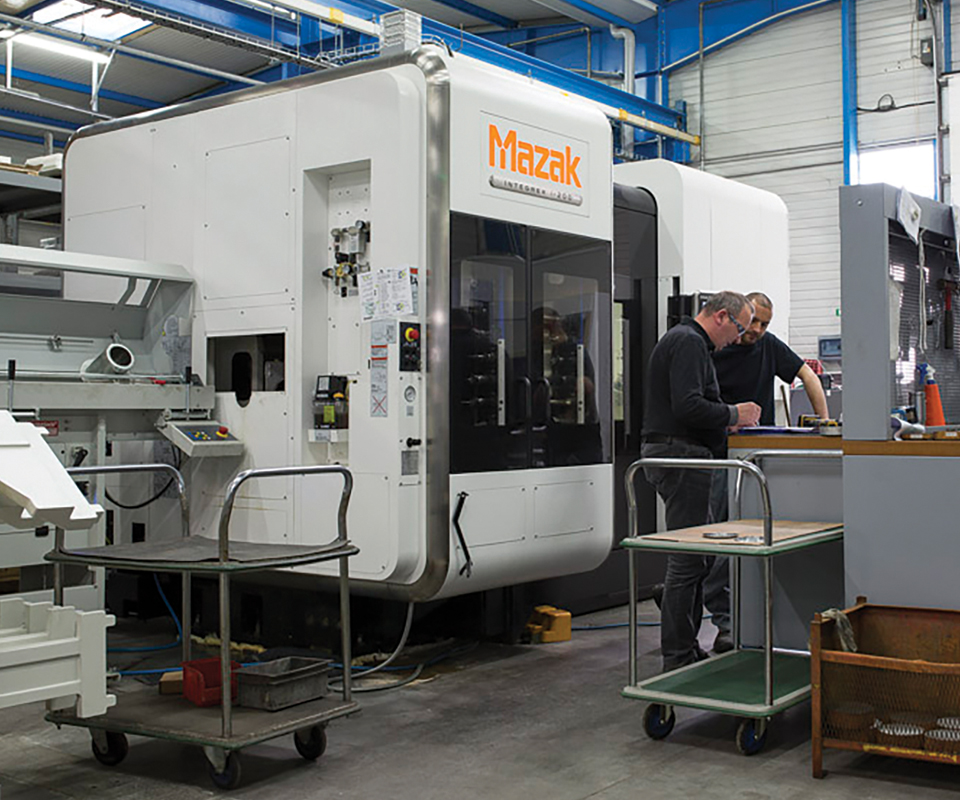 Two employees working at a workstation in front of a large machine tool.