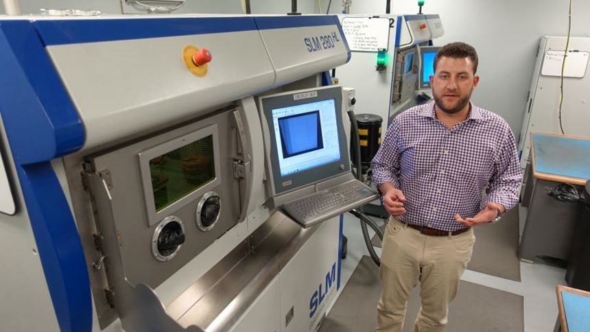 Christian Joest in front of the SLM Solutions machines used for 3d printing in a machine shop