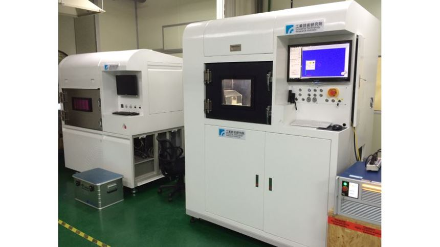 The powder-bed additive machine at right is near to commercialization. An earlier R&D model is seen at left.