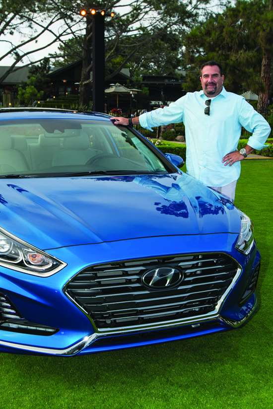 "Hyundai Design Center chief designer Chris Chapman and the 2018 Sonata. Note the chrome strip that separates the main and lower grilles, then cants downward below the air inlet/lighting cutouts on either side. Chapman describes it as the ""catamaran line."""