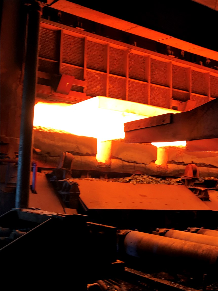 A rebuilt walking beam furnace discharges a slab onto rollers at ArcelorMittal's 80-inch hot strip mill.