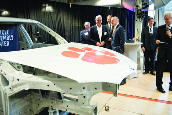 Knudt Flor, president and CEO of BMW Manufacturing (second from left), talks with Clemson President James P. Clements. Image Credit: Clemson University.
