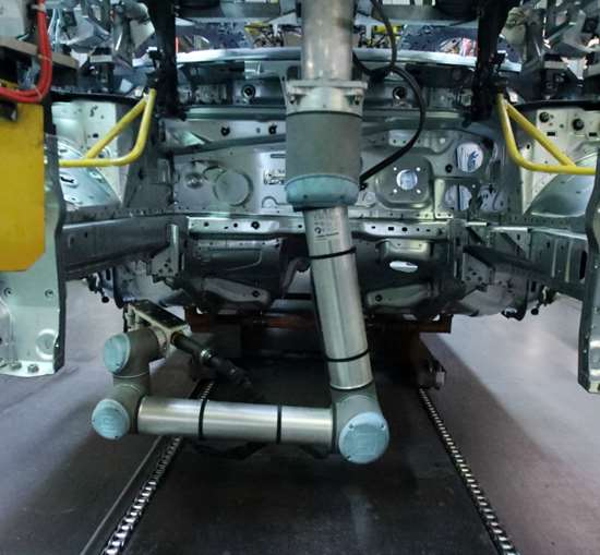 Universal Robots UR10 performs a screwdriving operation underneath a vehicle.