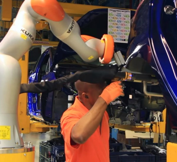 Kuka cobot positions a shock absorber into a wheel arch for installation.
